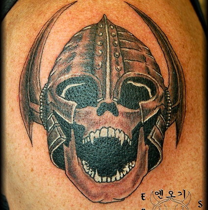 Grey Ink Helmet And Skull Tattoo On Biceps