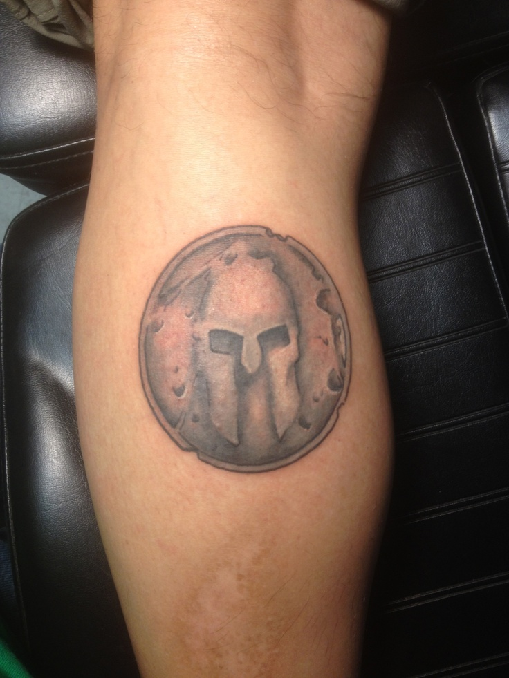 Grey Ink Helmet Tattoo On Leg