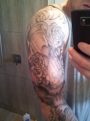 Grey Ink Hour Glass And Rose Tattoos On Sleeve