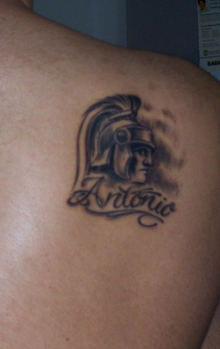 Grey Ink Spartan Head And Helmet Tattoos On Back Shoulder