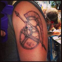 Grey Ink Spartan Helmet Tattoo On Biceps