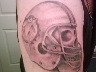 Grey Ink Sports Helmet Tattoo On Biceps