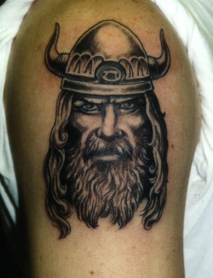 Grey Ink Viking Head In Helmet Tattoo On Biceps