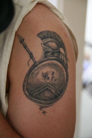 Grey Ink Warrior's Helmet And Equipments Tattoo On Biceps