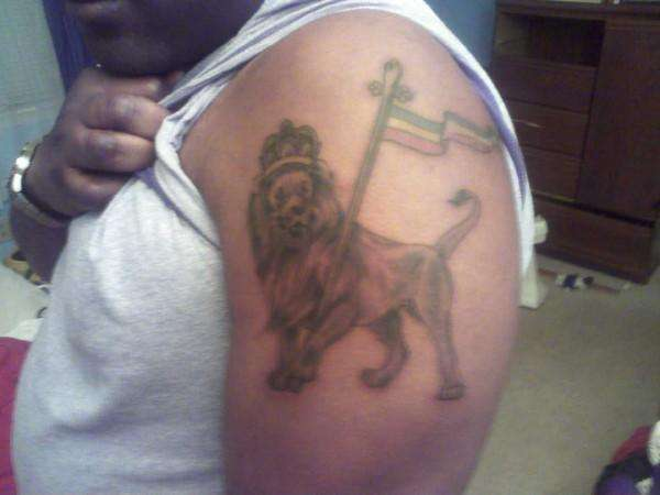 King Lion With Flag Tattoo On Biceps