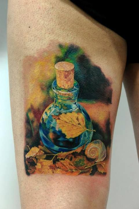 Leaf In Bottle Portrait Tattoo On Thigh