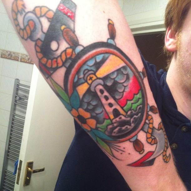 Lighthouse In Wheel Tattoo On Arm