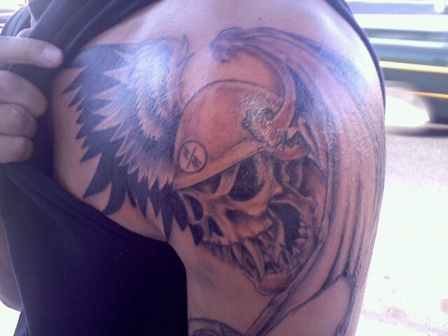 Man Shows His Winged Skull Helmet Tattoo