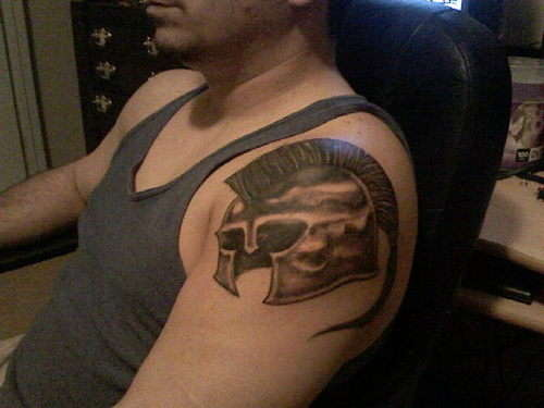 Man With Roman Helmet Tattoo On Shoulder