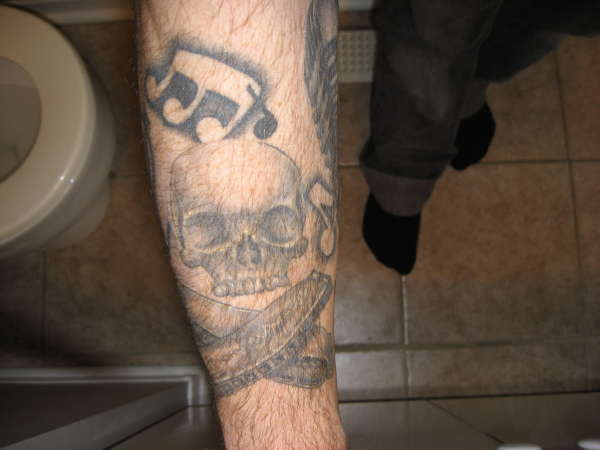 Music Notes Skull With Harmonica Cross Bones Tattoo On Leg