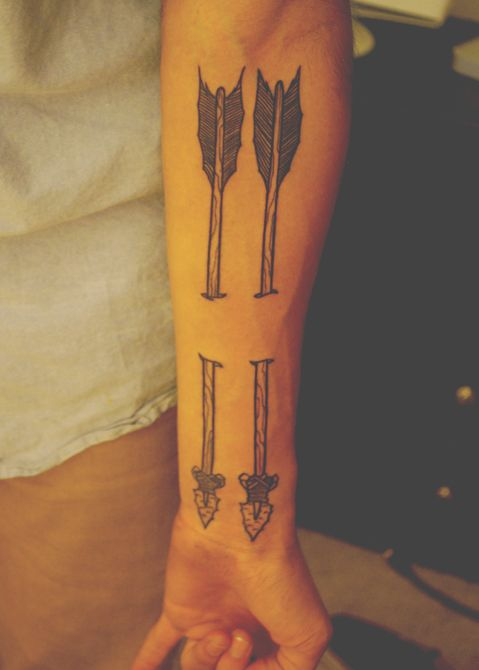 Old Ripped Skin Arrow Tattoo On Forearm