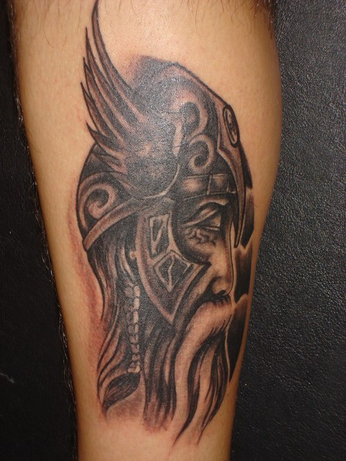 Old Viking Head In Grey Winged Helmet Tattoo