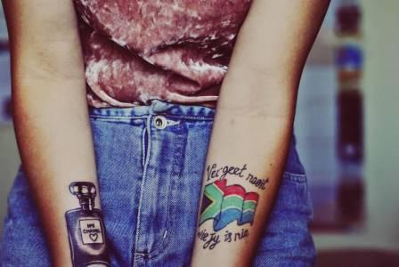 Perfume Bottle And Flag Tattoos On Forearm