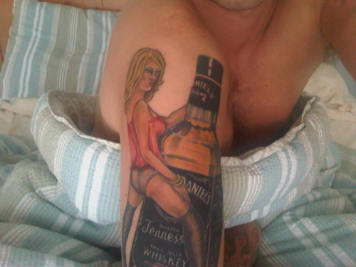 Pin Up Girl With Whiskey Bottle Tattoo On Arm