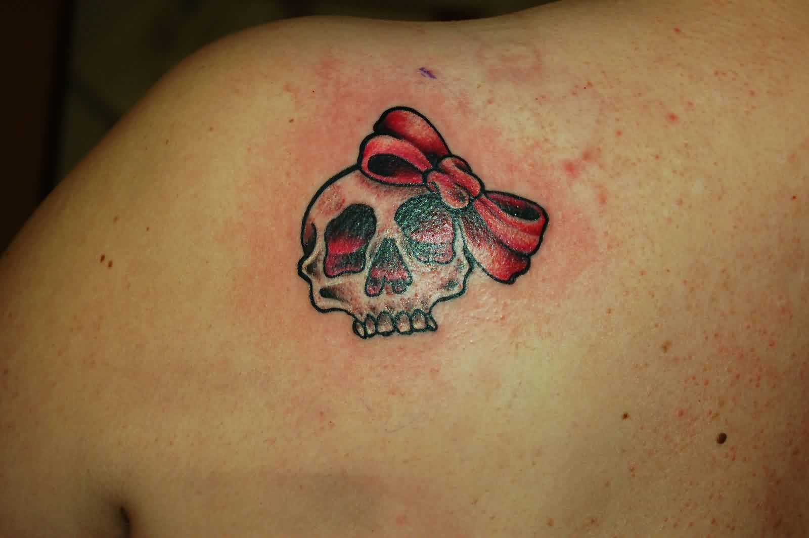 Skull With Ribbon Bow Tattoo On Back Shoulder