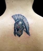 Small Helmet Tattoo On Upperback