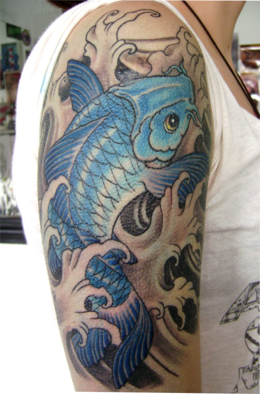 Amazing Blue Carp Fish And Wave Tattoo On Shoulder
