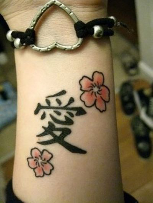 Black Ink Chinese Text And Cherry Blossom Tattoo On Wrist