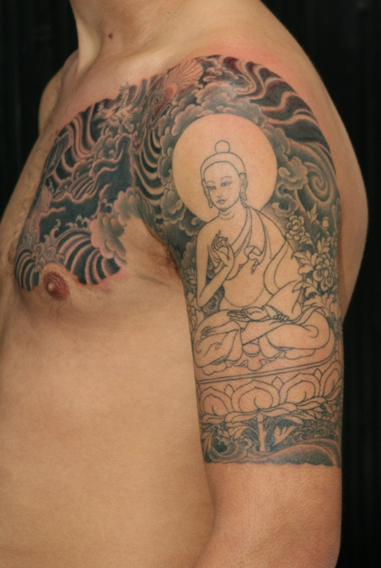 Grey Ink Buddhist And Lotus Flower Tattoo On Men Shoulder