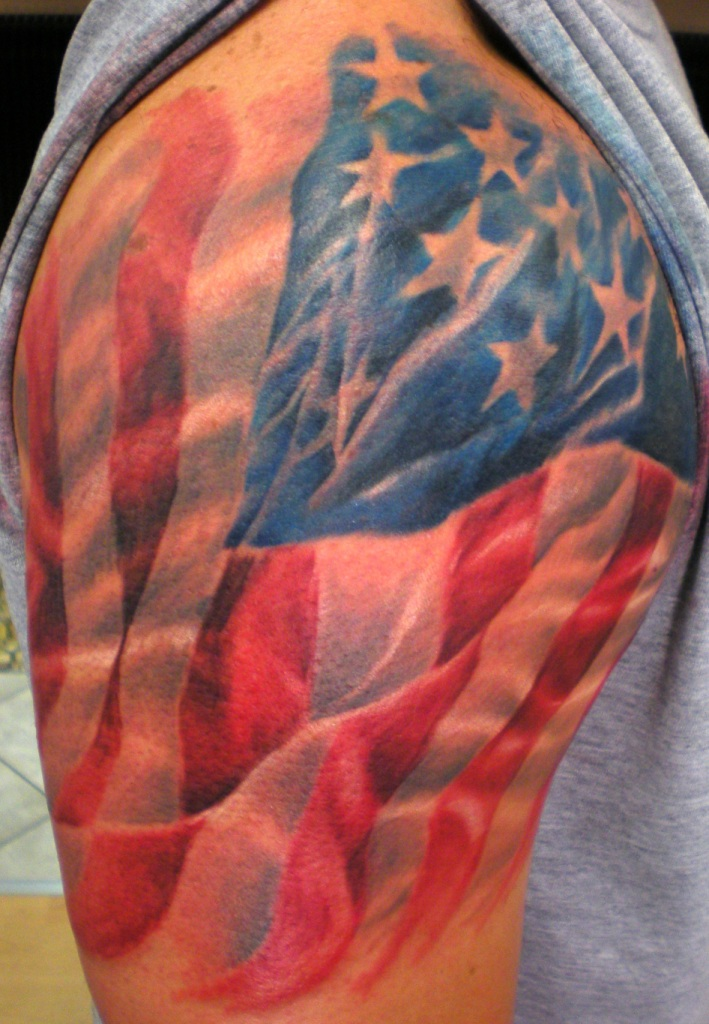 Red And Blue Ink Amazing American Flag Tattoo On Shoulder