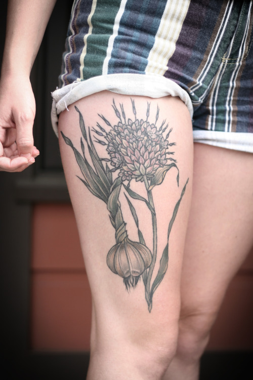Cool Animated Garlic And Flower Tattoo On Girl Thigh