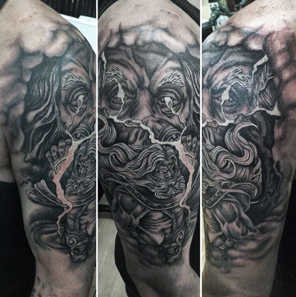 Dark Grey Ink Greek Men Face Tattoo On Shouldr