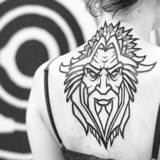 Angry Pegan God Tattoo On Girl Upper Back