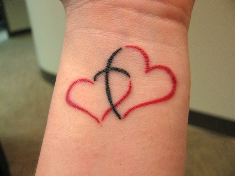 Black And Red Ink Nice Love Heart Tattoo On Wrist