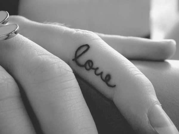 Black Ink Love Text Tattoo On Finger Of Girl
