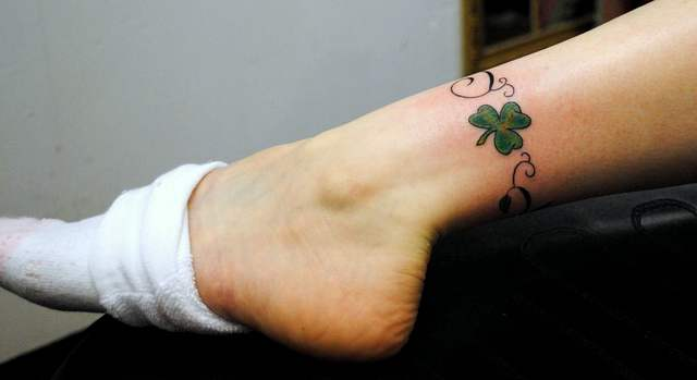 Girl Show Her Nice Shamrock Tattoo Design Near Ankle