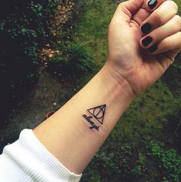 Girl Showing Her Black Ink Hallows With Text Tattoo