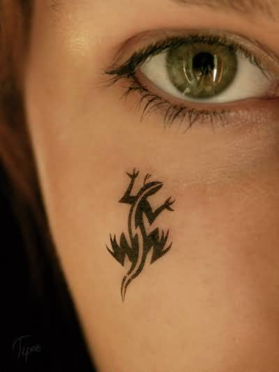 Girl Showing Her Black Ink Small Salamander Tattoo On Face