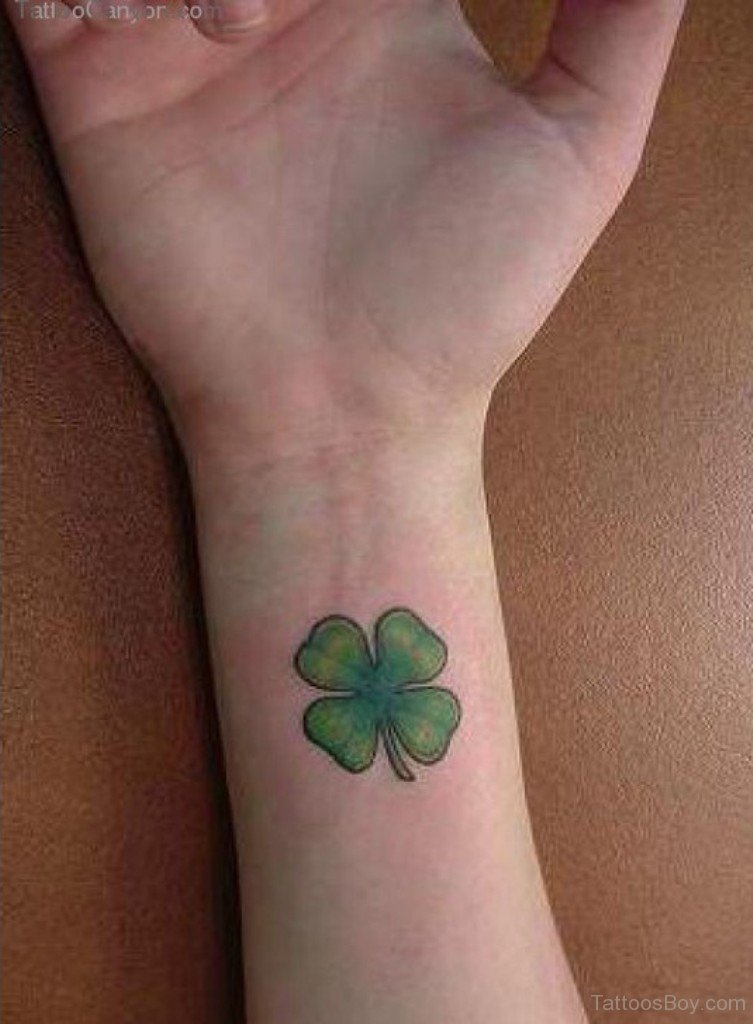 Green Ink Four Leafs Shamrock Tattoo On Girl Near Wrist