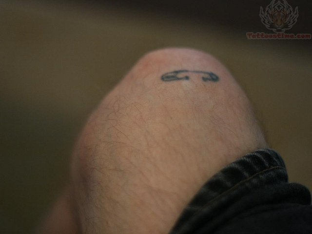 Grey Ink Simple Safety Pin Tattoo On Knee