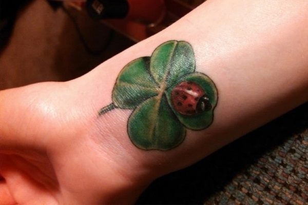 Lady Bug Sit On Nice Geeen Shamrock Tattoo On Wrist