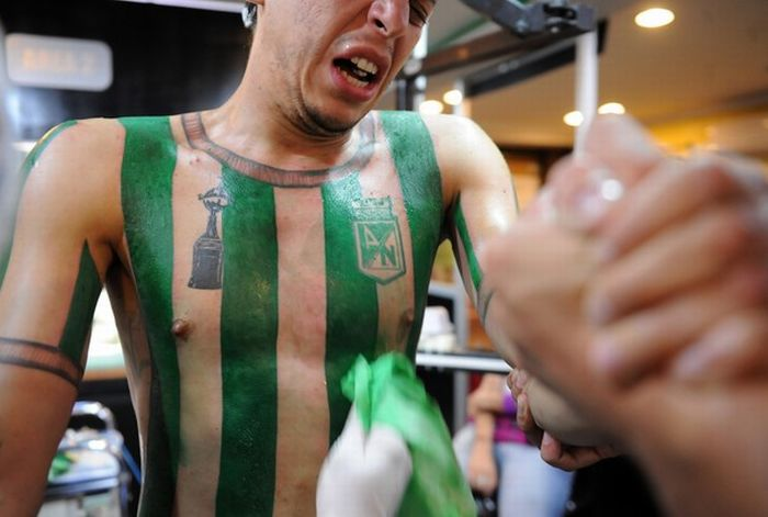 Colombian football fan Felipe Alvarez, 25, gestures while beiing tattooed with the Atletico Nacional jersey --which he made in honor of footballer Andres Escobar-- at a studio on October 9, 2010 in Medellin, Antioquia department, Colombia. AFP PHOTO/Raul ARBOLEDA (Photo credit should read RAUL ARBOLEDA/AFP/Getty Images)