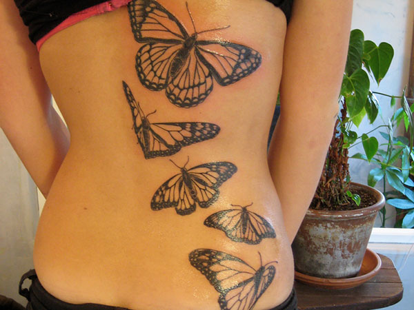 Nice Series Of Flying Monarch Butterfly Tattoo On Girl Back