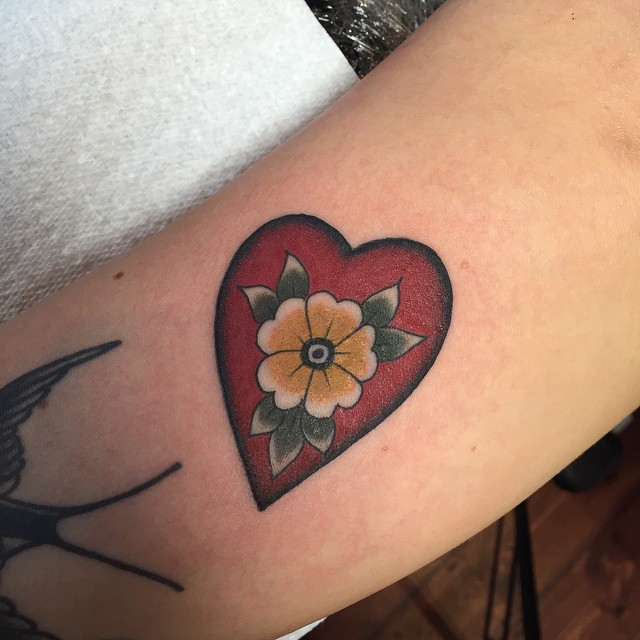 Nice Yellow Flower In Red Heart Tattoo