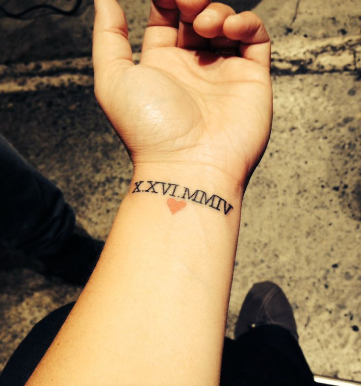 Red Small Heart With Nice Roman Numbers Tattoo On Wrist