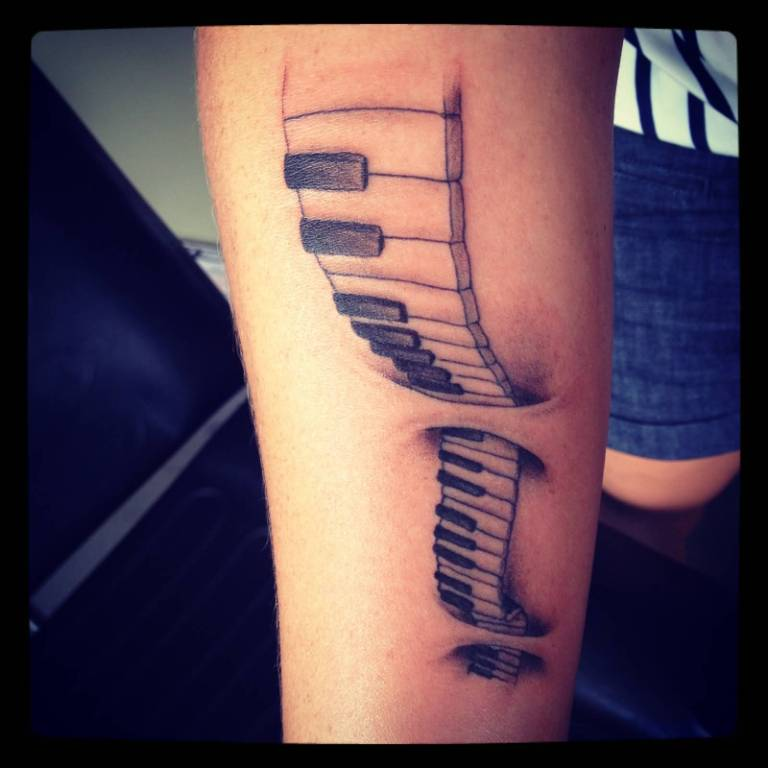 Ripped Skin Piano Keys Tattoo Design On Forearm