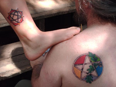 Small And Nice Colorful Pegan Star Tattoo On Upper Back
