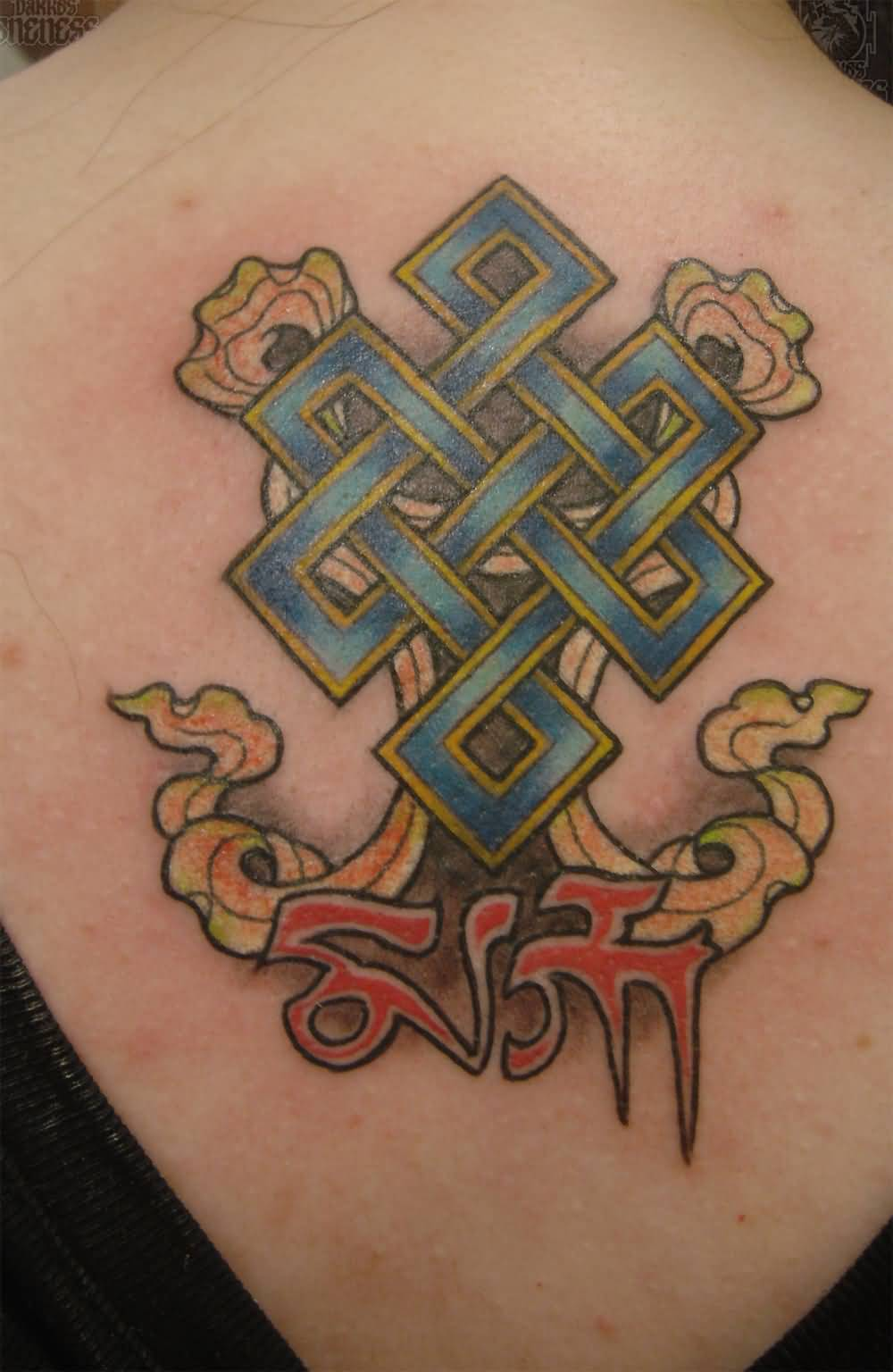 Tibetan Red Ink Letters With Nice Endless Knot Tattoo On Upper Back