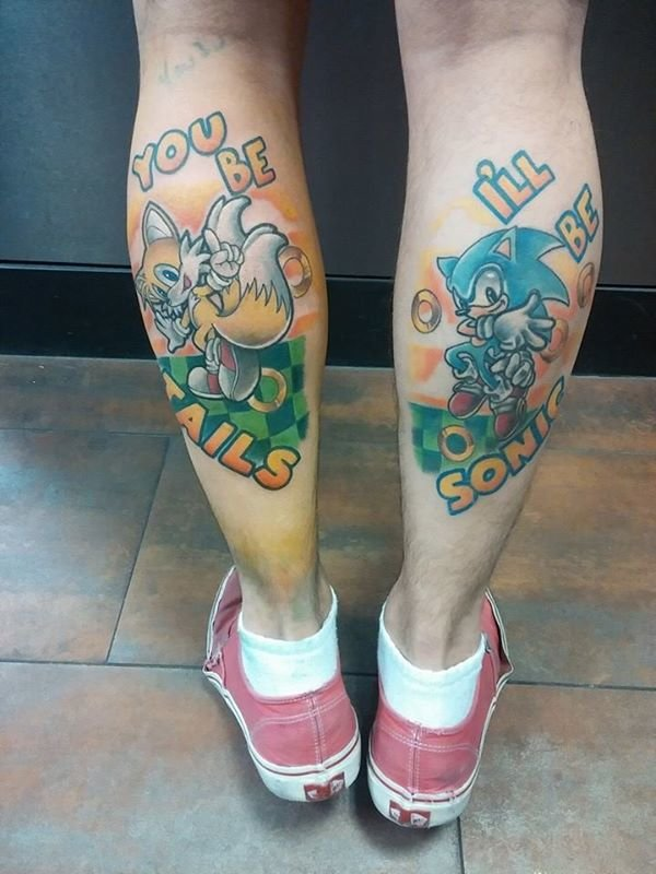Nice Sonic And Tails Text And Cartoon Tattoo On Girl Back Leg